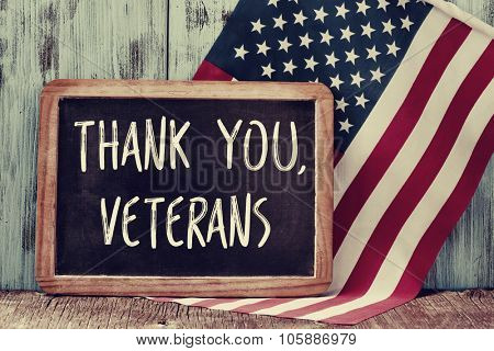 the text thank you veterans written in a chalkboard and a flag of the United States, on a rustic wooden background
