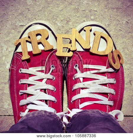 high-angle shot of some wooden letters forming the word trends and the feet of a man wearing red sneakers on the street poster