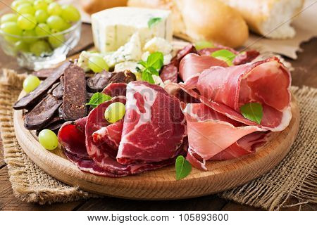 Antipasto catering platter with bacon, jerky, sausage, blue cheese and grapes on a wooden background