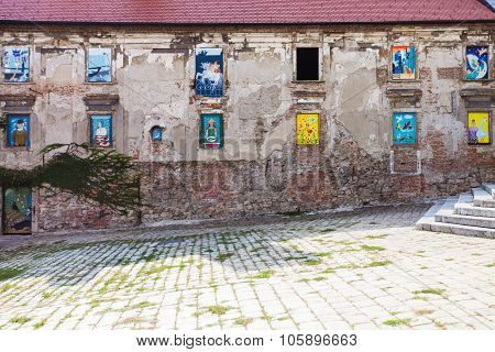 Neglected House With Mural Paintings In Windows