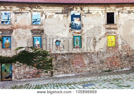 Abandoned House With Paintings In Windows