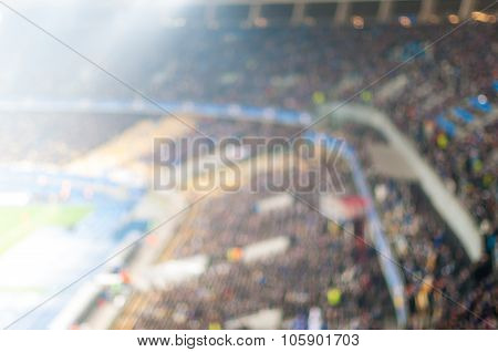 Blurred crowded football stadium. View Of the floodlit tribune of sport arena. Background with empty