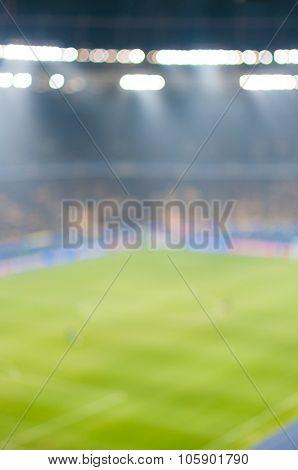 Blurred Green soccer field, bright spotlights, illuminated stadium