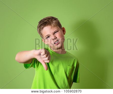 Portrait unhappy, angry, displeased child giving thumbs down hand gesture, isolated on green backgro