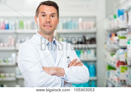 Portrait of confident mid adult male pharmacist with arms crossed standing in pharmacy