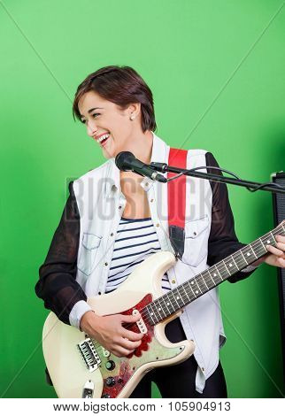 Happy female signer playing guitar while singing in recording studio