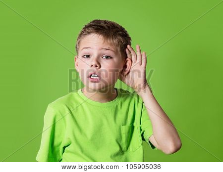 Curious boy listens. Closeup portrait child hearing something, parents talk, gossips, hand to ear ge