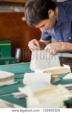 Mid adult male worker binding book at table in paper factory