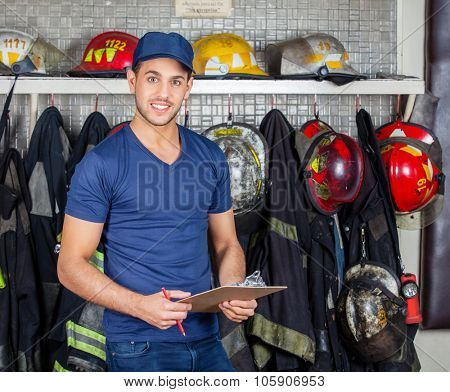 Portrait of confident firefighter holding clipboard at fire station poster
