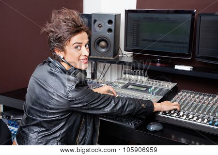 Portrait of confident young woman mixing audio in recording studio