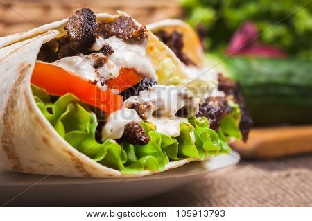 Tasty fresh wrap sandwich with beef vegetables and tzatziki sauce poster