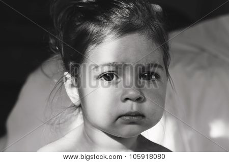 Toned Portrait of cute sad baby girl thinking.