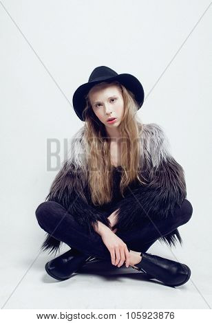 young blonde teenage girl in hat and fur coat, fashion dressed model, studio shot