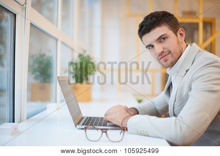 Handsome Man Using Computer On Workplace