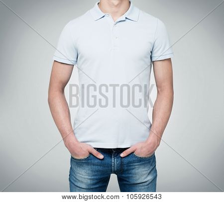 A Man In A Light Blue Polo Shirt And Denims Holds His Hands In Pockets. Grey Background.