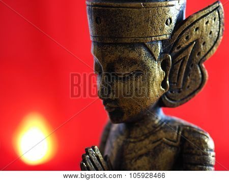 Gold Buddha Praying with Red Background and flame