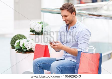 Cheerful father holding mobile phone