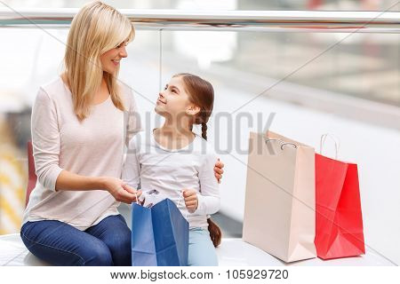 Mother with daughter sitting on the bench