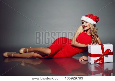 Sexy Blonde Santa In A Red Dress Posing With Christmas Present