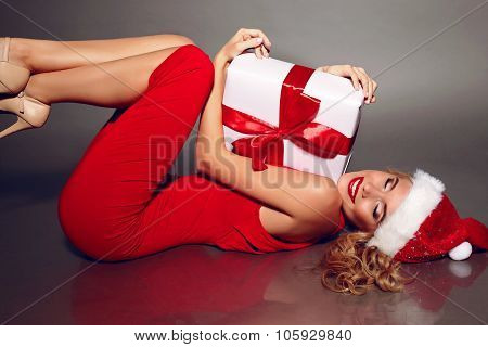 Sexy Blonde Santa In A Red Dress Holding Christmas Present