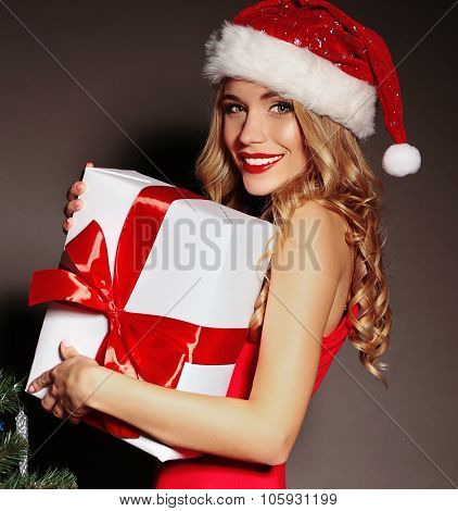 Sexy Blonde Santa In A Red Dress With Red Lipstick And A Beautiful Smile Holding A Box With A Gift N