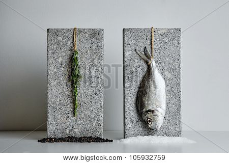 Dorada And Rosemary Presented On Stone Bricks With Sea Salt And Black Pepper