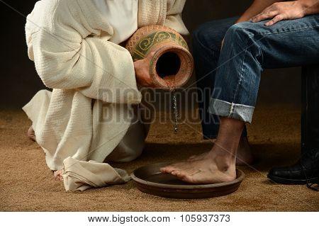 Jesus pouring water to wash feet of modern man over dark background