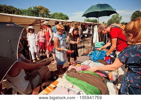 Crowd Of People Watching Old Clothes Of Second Hand Market