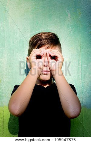 A boy using hands like glasses on green background