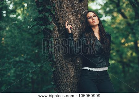 Lonely Woman Posing Leaning On A Tree