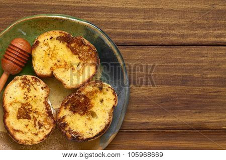 French toast made of baguette with honey honey dipper on the side photographed overhead on dark wood with natural light poster