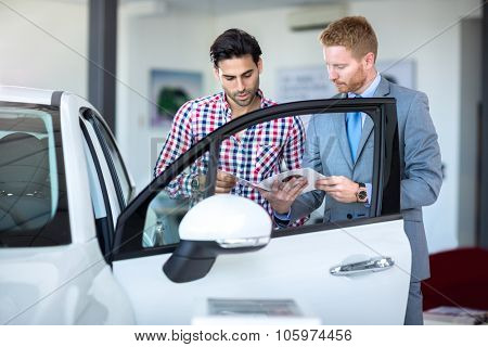 Car salesperson demonstrating a new automobile to young man