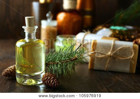 Essential oil of pine, handmade soap and cream with pine extract and spa treatments on wooden background poster