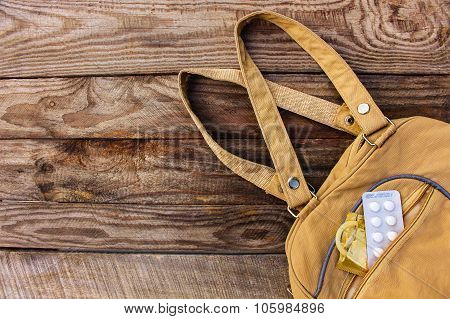 The birth control pill and condom falls out of pocket with handbags on wooden background. Toned imag