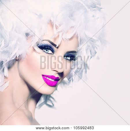 Beauty Holiday makeup. Fashion Model Girl with White Feathers Hair style and bright make up. Beautiful woman with feathers on her head. Hairstyle. Holiday Creative Makeup