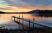 This old rickety timber plank jetty juts out into Wallaga Lake the largest lake in southern NSW. The sunset beyond painting the sky and colouring the tranquil waters in soft hues of red and blue. poster