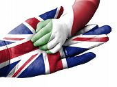 Flag of United Kingdom overlaid the hand of an adult man holding a baby hand with the flag of Italy overprinted. Conceptual image for help aid assistance rescue. Isolated on white background poster