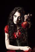 Horror shot: the strange scary girl with mouth sewn shut holds apple studded with nails poster