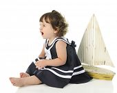 Profile of an adorable little girl angrily growing while sitting barefoot in her sailor dress.  A toy sailboat is behind her.  On a white background. poster
