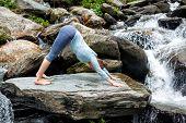 Young sporty fit woman doing yoga asana Adho mukha svanasana - downward facing dog - at tropical waterfall poster
