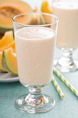 Healthy cantaloupe smoothie in a tall glass with fresh cantaloupe poster