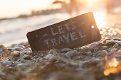 Lets go travel adventure motivation concept. Sign with the text Let's Travel on the beach sunset. poster