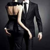 Conceptual portrait of a young couple in elegant evening dresses poster