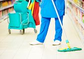 cleaning services. female cleaner in uniform  with mop the floor in supermarket shop store poster