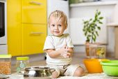 Playful child boy with kitchenware and foodstuffs on floor in kitchen poster