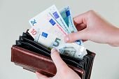 in a purse there are several euro banknotes.  poster