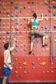 Instructor guiding woman on rock climbing wall at the gym poster