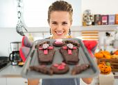Portrait of smiling housewife in decorated kitchen showing off freshly baked Halloween biscuits for Trick or Treat. Ready to halloween party. Traditional autumn holiday poster