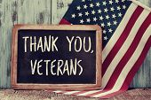the text thank you veterans written in a chalkboard and a flag of the United States, on a rustic wooden background poster