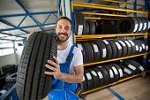 smiling auto mechanic carrying tire in tire store poster